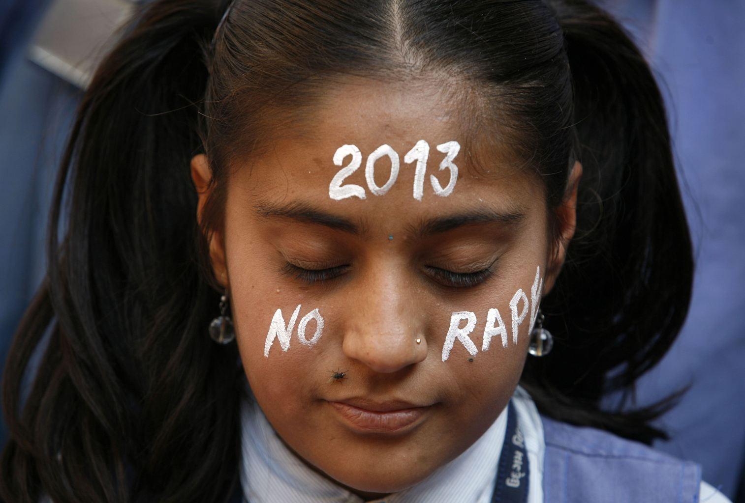 一名印度女孩,在黑公交輪姦案受害者悼念會中,在臉上寫上 2013 零強姦的祝願。攝影:AMIT DAVE / REUTERS